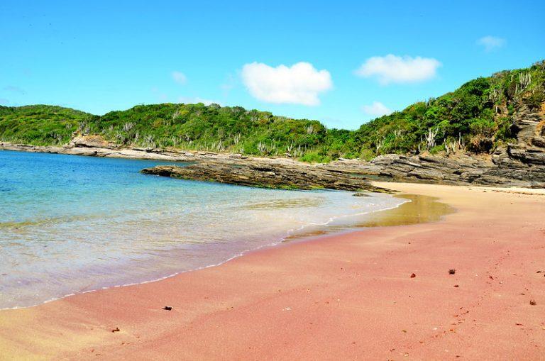 Mar azul e areia vermelha formam a paisagem exótica da Praia do Forno, em Arraial do Cabo