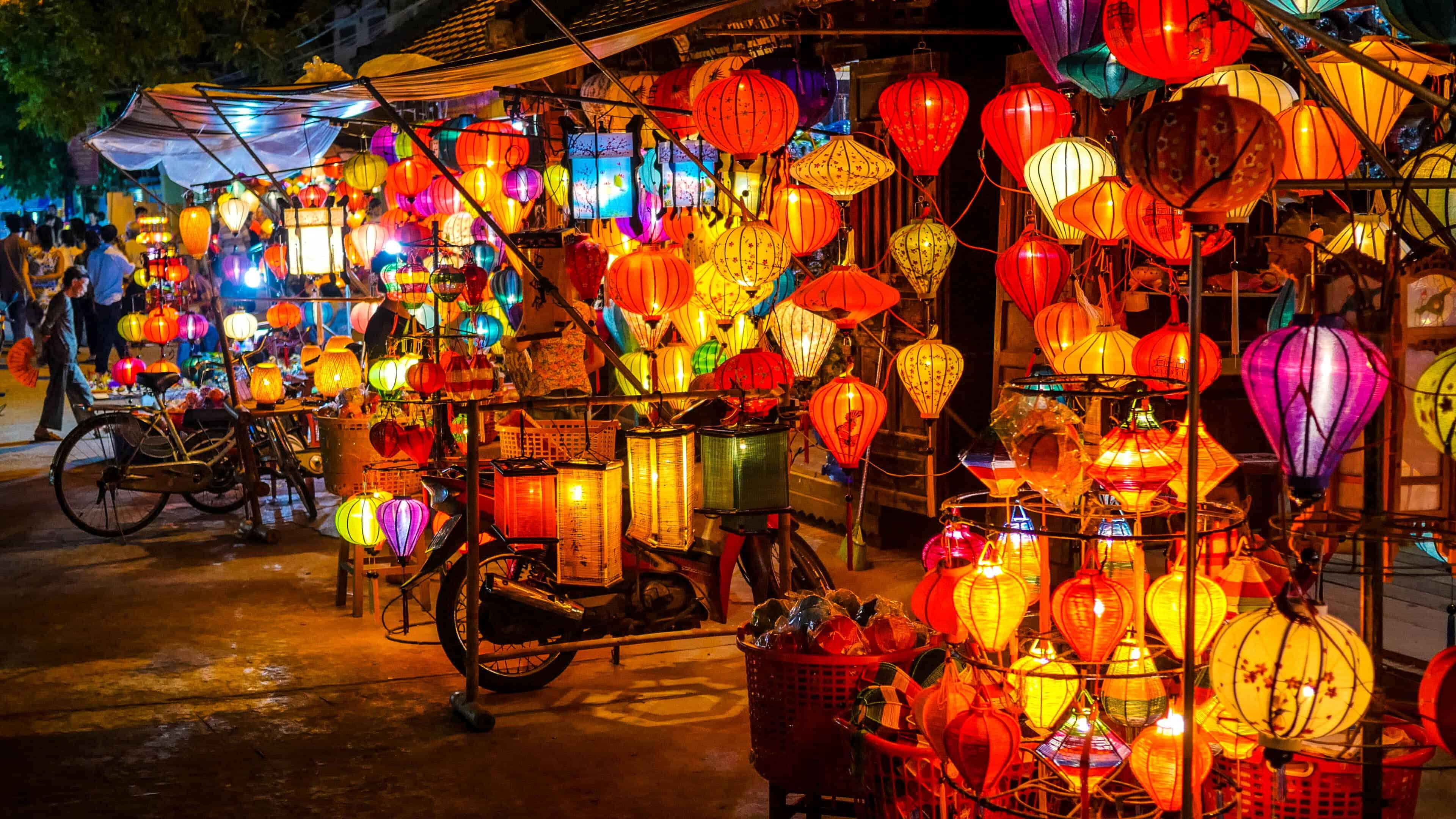 Na foto, vemos uma fileira de barracas cheias de lanternas iluminadas