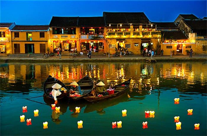 Na foto vemos três pessoas, cada uma num barco, vestindo trajes tipicamente asiáticos, colocando lanternas flutuantes sob o rio de Hôi An