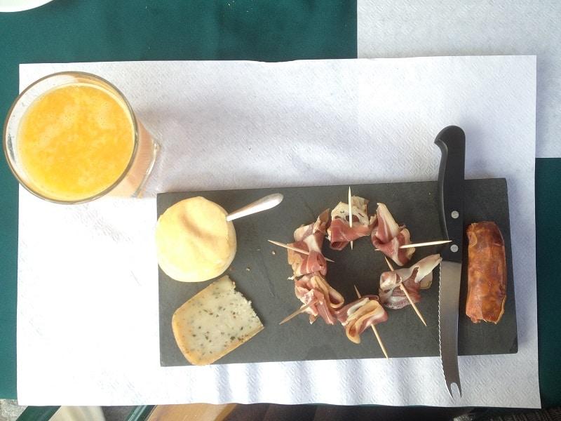 Mesa com suco e quatro variedades de embutidos portugueses, sendo dois tipos de queijos, um presunto e um salame