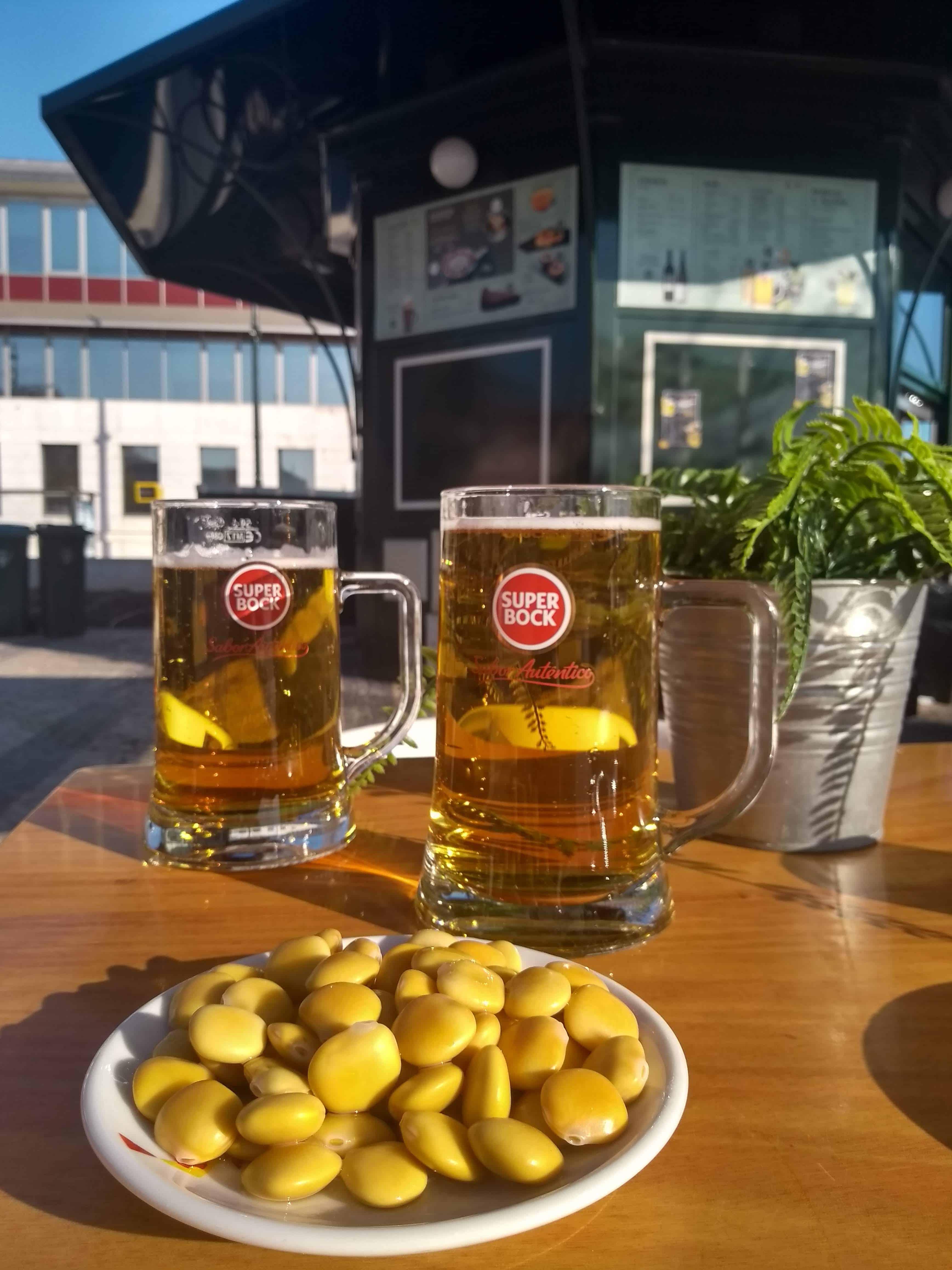 Porção de tremoços acompanhada de dois copos de cerveja da marca Super Bock