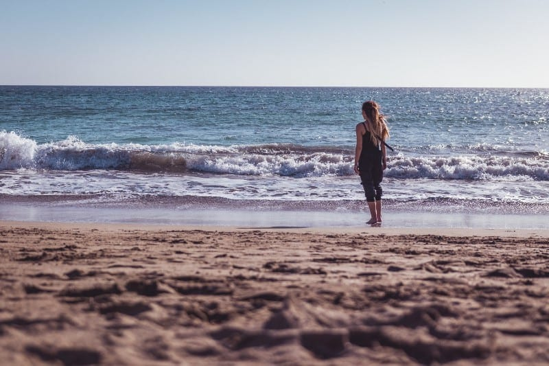 Mulher de costas na beira da praia