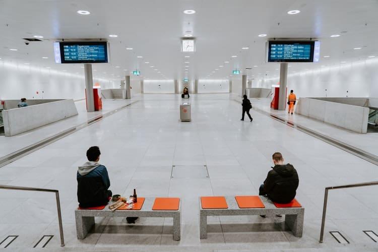 Duas pessoas esperam sentadas em um banco no aeroporto