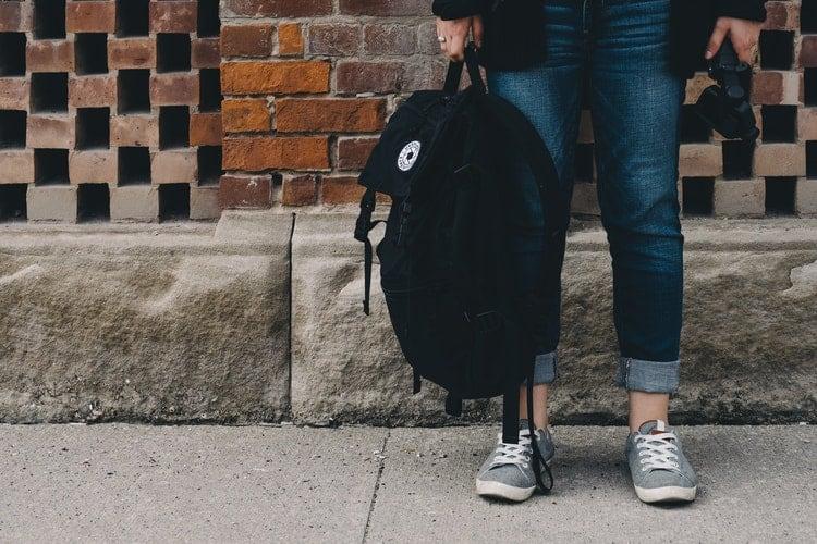 Pessoa segurando uma mochila preta