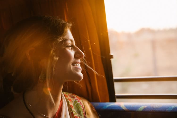 Mulher sorridente ao viajar de ônibus pela Europa