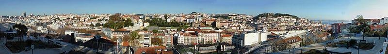 """<strong>Vista panorâmica de Lisboa a partir do Miradouro de São Pedro de Alcântara</strong>. Foto <a href=""""https://creativecommons.org/licenses/by-sa/4.0/deed.en"""" target=""""_blank"""" rel=""""noopener"""">CC BY-SA 4.0</a> <a href=""""https://commons.wikimedia.org/wiki/File:Sao_Pedro_de_Alcantara_Belvedere,_Lisbon.jpg"""" target=""""_blank"""" rel=""""noopener"""">Reino Baptista</a>"""