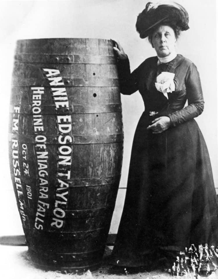 Annie Edson Taylor posa ao lado de seu barril em uma foto em preto e branco.