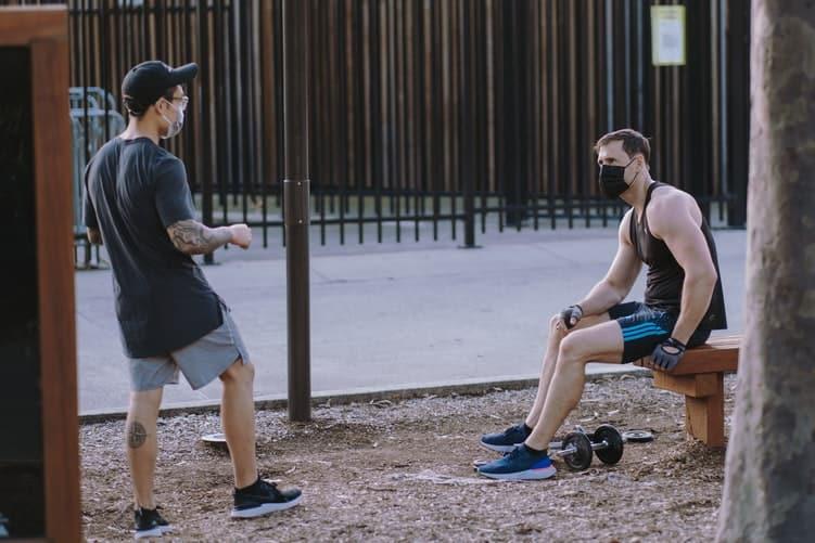 Dois jovens usam máscaras enquanto fazem esportes em um parque.