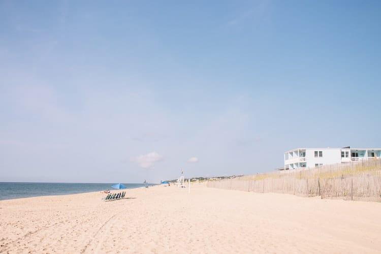 Praia de areias claras com algumas cadeiras próximas à beira do mar.