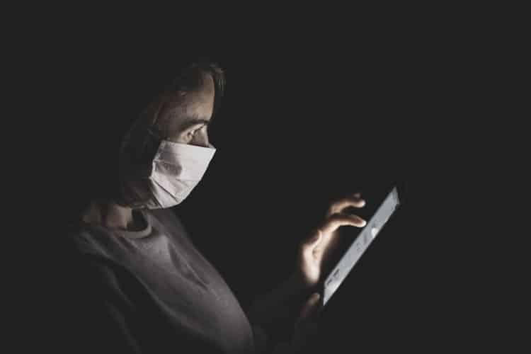 Mulher de máscara mexe no celular