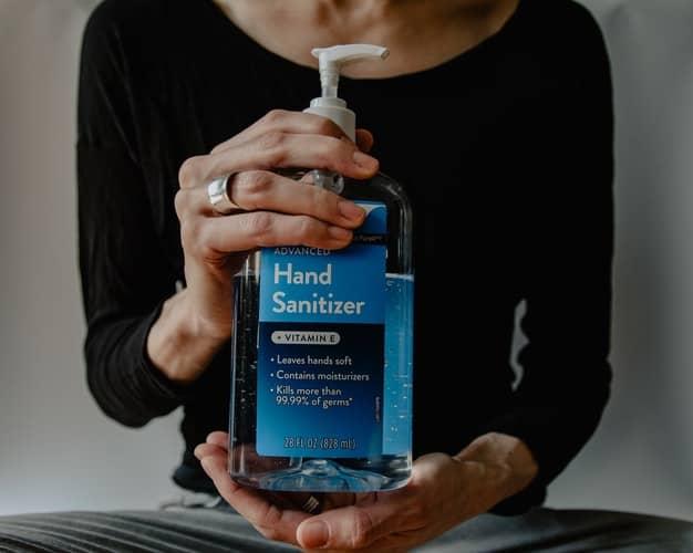 Pessoa segura desinfetante para mãos