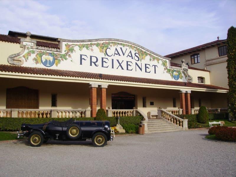 """Porta de uma construção onde se lê as palavras """"Cavas Freixenet"""" na fachada."""