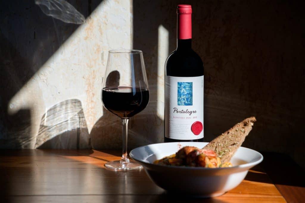 Garrafa e taça de vinho alentejano ao lado de um prato fundo de comida.