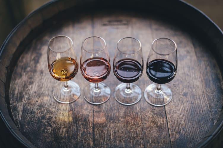 Quatro taças de vinhos portugueses lado a lado sobre um barril